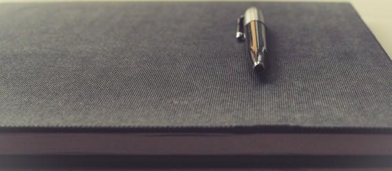 Notizbuch mit darauf gelegtem Stift - Vertriebsberatung