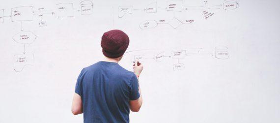 Mann vor whiteboard entwickelt Vertriebsstrategie - Vertriebsberatung